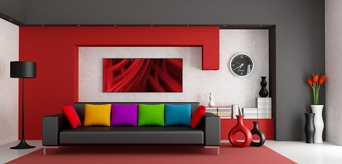 a modern living room with a black couch and colorful pillows and a red statement wall