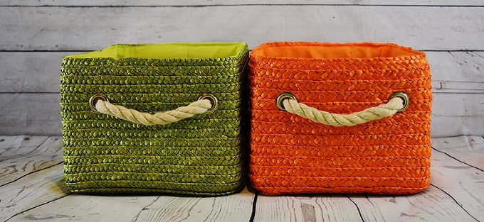 a green storage basket next to an orange one, both placed on the floor, on a wooden surface