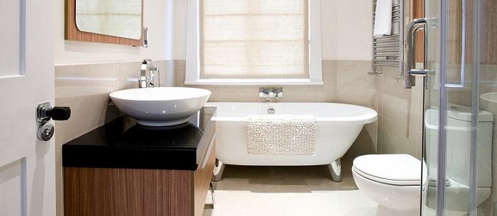 a modern elegant small bathroom with a window above the bathtub