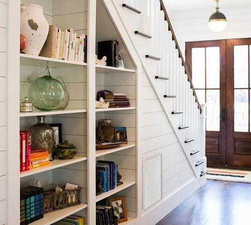 white shelves under white stairs in a large home