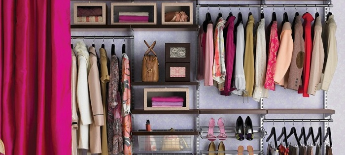 a large organized closet with many clothing items that are a certain shade of pink