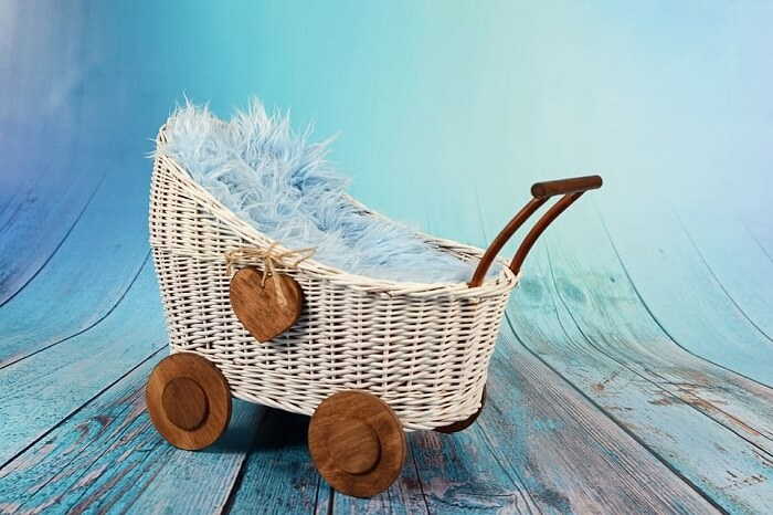 empty rattan stroller with wooden handle, wheels, and heart-shaped accessory