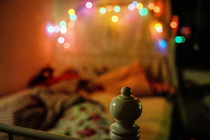 whimsical lights in teenage bedroom above bed at night