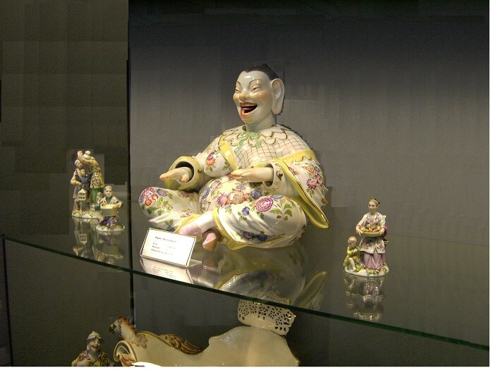 porcelain laughing buddha statue on shelf
