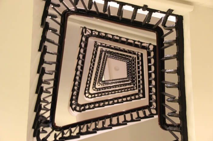 white staircase with black banisters seen from down upwards