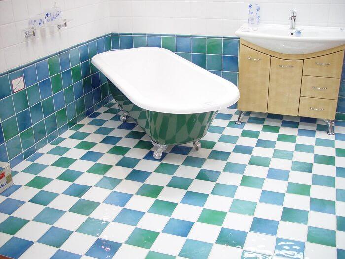 bathroom on green, blue, white tiles with freestanding bath tub