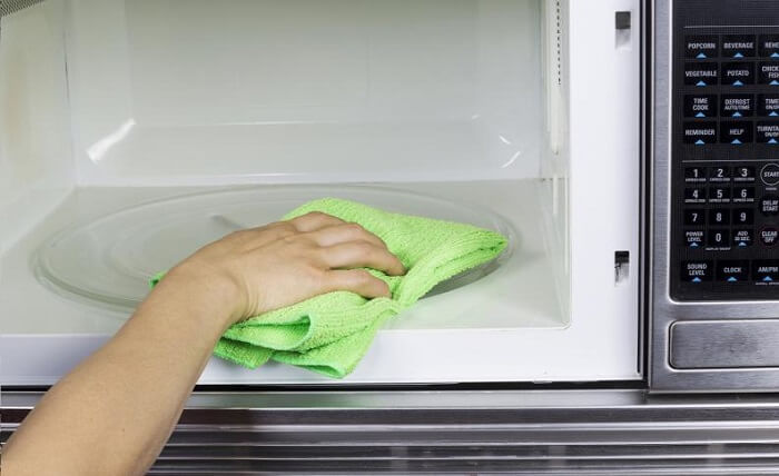person cleaning microwave interior with clean rag