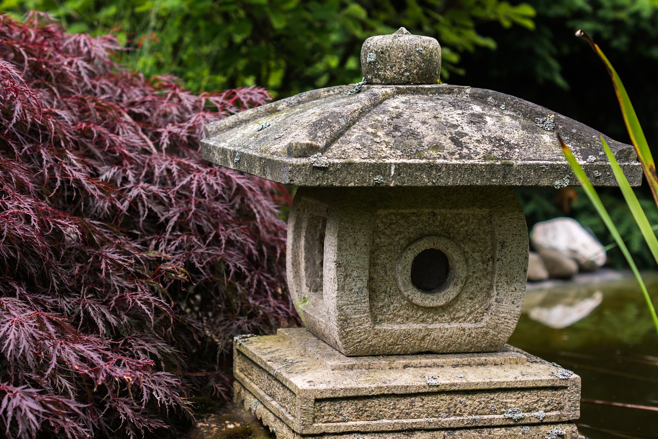 a feng shui  stone lantern placed in the garden near a pond