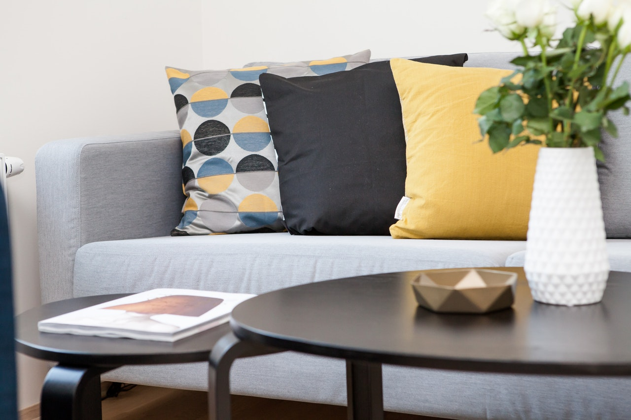 Centerpiece on coffee table beside sofa with three pillows