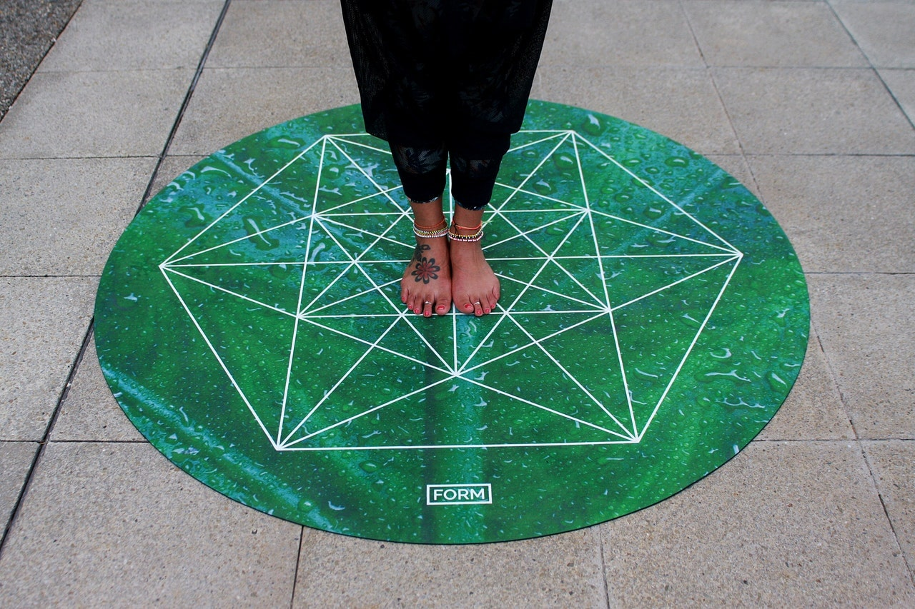 Person standing on green yoga mat